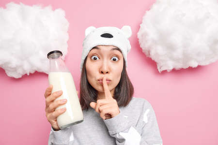 Surprised Asian girl makes silence gesture presses index finger to lips tells secret going to prepare breakfast from milk dressed in nightwear poses against rosy background. Hush be quiet please