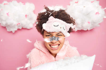Emotional curly woman clenches teeth feels angry after pillow fight poses under feathers flying around wears sleepmask applies patch on nose to reduce blackheads isolated over pink background Stock fotó