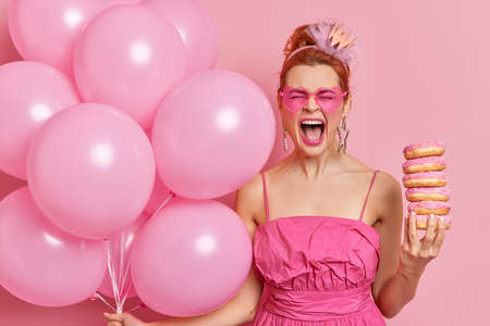 Emotional redhead young woman exclaims loudly keeps mouth widely opened comes on birtday party to congratulate friend with anniversary holds bunch of helium balloons and doughnuts poses indoor