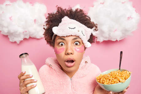 Beautiful shocked African American woman stares surprisingly at camera keeps mouth opened ha breakfast in morning hears unbelievable news wears sleepwear reduces fine lines under eyes with pads