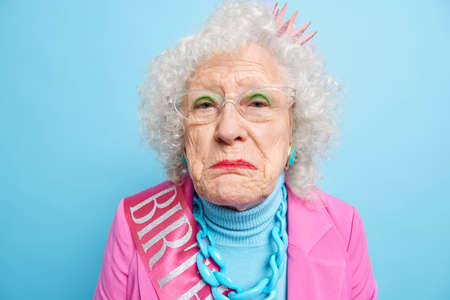 Displeased lonely retired old woman has wrinkled well cared face looks disappointed and gloomy celebrates birthday alone dressed in stylish clothes isolated over blue background. Close up shot