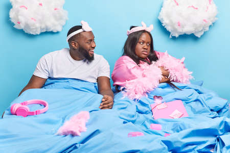 Offended dark skinned overweight woman turns from husband has sullen expression wears dressing gown being angry after hearing insulting words pose in bed sort out relationships. Break up concept