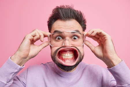 Startled handsome man stares surprisingly through transparent spectacles clenches teeth has widely opened mouth hears great news stands alarmed being super shocked stands indoor. Emotions concept Foto de archivo