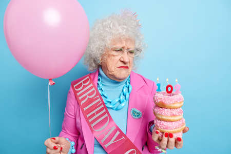 Distressed unhappy elderly woman being upset about getting older holds pile of glazed doughnuts celebrates birthday alone feels lonely dressed in fashionable clothes poses with balloon indoor