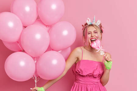 Cheerful blonde woman has party mood bites heart shaped lollipop keeps mouth wide opened wears stylish dress holds bunch of inflated balloons isolated over pink background. Birthday celebration