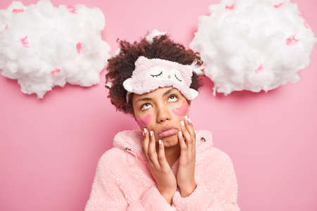 Image of African American woman being fed up of morning routines keeps hands on cheeks looks with bored tird expression upwards dressed in pajama isolated over pink background white clouds up