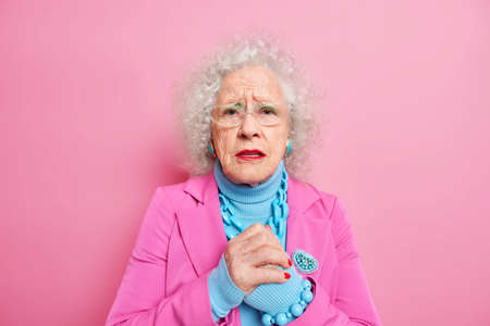 Worried elderly woman with wrinkled face keeps hands together looks disappointed feels nervous about something wears spectacles fashionable clothes isolated over pink background. Old female indoor
