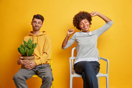 Relaxed cheerful Afro American woman stretches arms poses on comfortable chair feels glad to finish all necessary work. Displeased puzzled guy holds pot of cactus isolated over yellow background