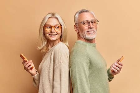 Mature woman and man stand back to each other have fun together use phones for scrolling social networks dressed casually surf internet isolated over brown background. Elderly couple with gadgets Standard-Bild