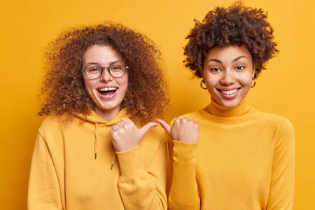 Happy joyful mixed race curly haired women point at each other with cheerful expression say its she stand closely to each other dressed casually isolated over yellow background. I choose you