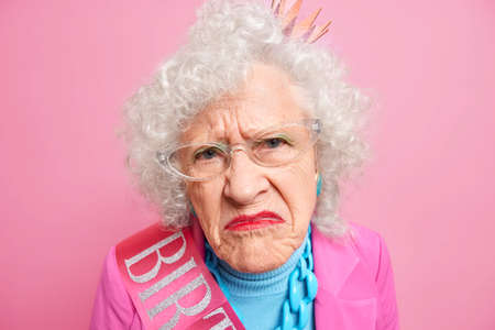 Close up shot of displeased wrinkled grandmother smirks face looks unhappily at camera has bright makeup being discontent with something isolated over pink background. Negative emotions concept