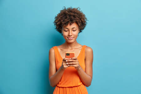 Photo of satisfied young African American woman checks newsfeed on smartphone wears dress poses with shoulders uses high speed internet being always in touch isolated over blue background