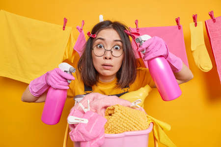 Surprised Asian woman looks stunned at camera holds two bottles of detergents cleans everything in house does laundry with effective washing liquid has clothespins on hair. Housekeeping concept