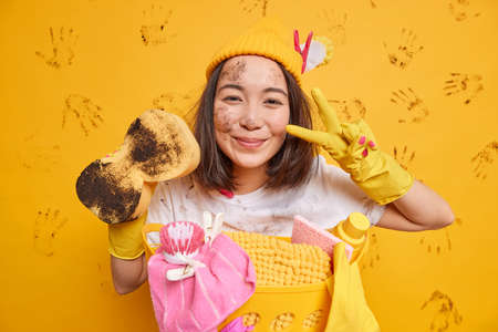 Household chores concept. Pleased Asian housewife makes peace gesture wears protective rubber gloves holds muddy sponge poses dirty does laundry busy with regular clean up washes everything.