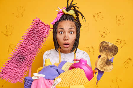 Household duties concept. Speechless impressed dark skinned woman has combed braids stares with omg expression cleans everything hols dirty cleaning equipment does washing isolated over yellow wall