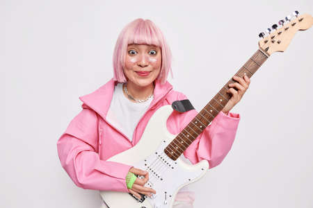 Horizontal shot of positive female guitar player with pink hair plays metal music on acoustic guitar dressed in stylish clothes isolated over white background. Hard rock concept. Talented frontwoman