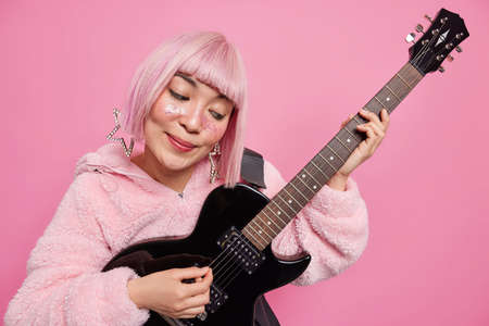 Woman pop band singer plays acoustic electric guitar wears fashionable clothes poses against pink background has trendy hairstyle. Popular guitarist creats new popular song acts like rock star