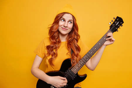 Young pretty woman with red hair enjoys playing acoustic guitar has dreamy pleased expression entertains friends wears casual t shirt and hat isolated over yellow background. Monochrome shot Stock Photo
