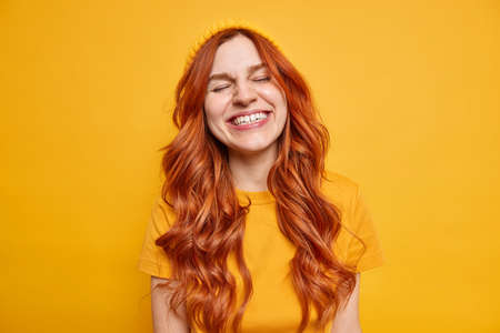 Portrait of vivacious joyful redhead woman grins at camera keeps eyes closed dressed in casual t shirt and hat shows authentic emotions stands relaxed over yellow background has fun. Monochrome shot
