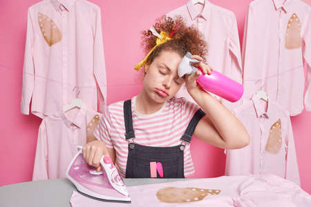 Overworked sleepy woman housekeeper wipes forehead feels fatigue while doing housework irons clothes does domestic chores holds spray bottle burned shirt being in hurry to finish everything.