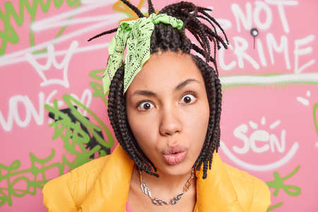 Close up shot of young adult looks with great wonder and surprisement in camera reacts on amazing news has braided hairstyle dressed in vest spends free time at street poses against graffiti wall