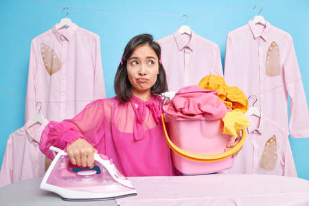 Housekeeping and daily routines concept. Dissatisfied brunette young Asian woman holds bucket of laundly being fed up of housework stands near ironing board. Sad housewife strokes linen at home Banque d'images