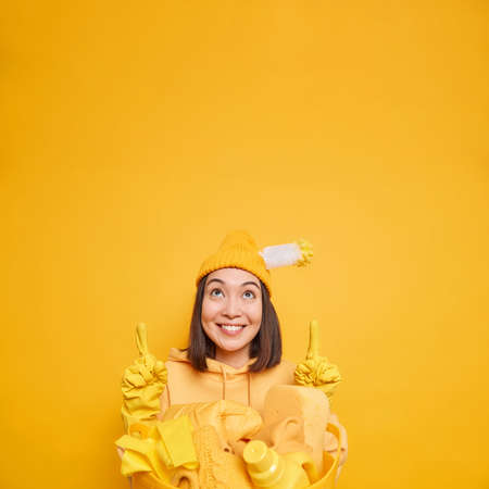 Happy Asian female janitor points above on blank space carries cleaning supplies in laundry basket demonstrates best product for housekeeping wears hat rubber gloves isolated over yellow wall