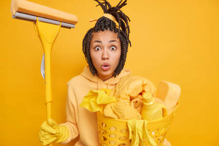 Housework and household chores concept. Startled dark skinned woman wife does laundry and washes everything at home holds mop for cleaning wears hoodie and protective rubber gloves on hands.