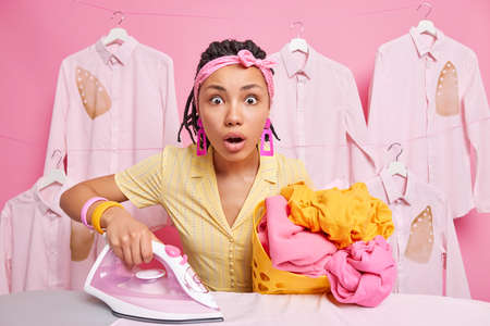 Shocked housewife stares surprisingly at camera holds basket of laundry and electric iron has much domestic work stands near ironing board wears headband. Housekeeping and daily routines concept