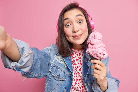 Attractive surprised funny Asian millennial woman with dark hair takes selfie makes photo of herself for social networks holds delicious ice cream listens favorite music via headphones. Leisure hobby