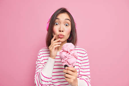 Studio shot of surprised young Asian woman has dark hair keeps lips rounded holds big yummy ice cream enjoys listening music via headphones wears striped jumper isolated over pink backgound.