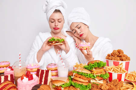 Unhappy young women tempting to eats something delicious surrounded by junk food keep to diet and healthy nutrition feel hungry look sadly at tasty burger sweet doughnut. Overeating concept.