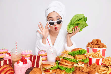 Funny young Asian woman makes fish lipsgrimaces at camera wears sunglasses dressing gown and bath towel over head holds green vegetable chooses healty food instead of fast food keeps to diet