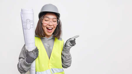 Professional Asian female construction engineer inspects enterprise holds rolled blueprints wears uniform safety helmet and helmet laughs positively points on blank space over white background Stock fotó