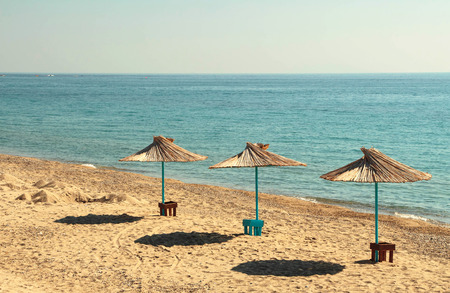 sun umbrellas: Three sun umbrellas by the beach