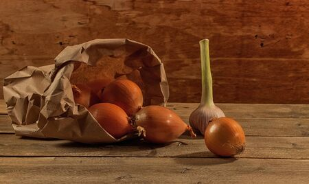 pealing: Against the background of old boards is garlic and onion in a kraft bag Stock Photo