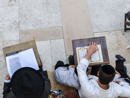 Two Jewish people praying the Torah. One of them is wearing a kipa and the other man is wearing a hat.