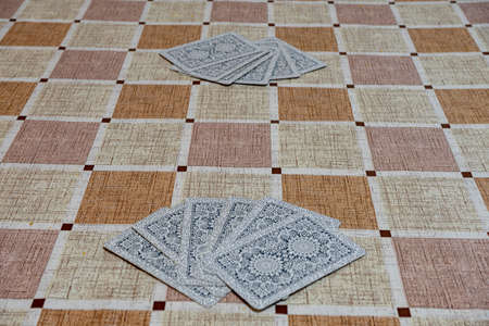 Deck of cards spread out on a table with a checkered tablecloth. Imagens