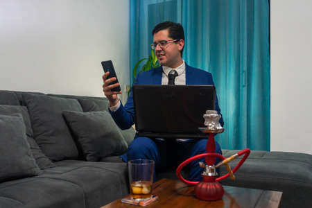 Young man sitting on a sofa. He is wearing a blue suit. He is working with his laptop and looking at his mobile. On a wooden table there is a glass of whiskey and a red shisha.