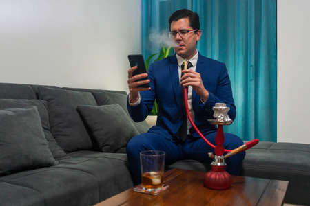 Young man sitting on a couch. He is wearing a blue suit. He is looking at his mobile. On a wooden table there is a glass of whiskey and a red hooka. Imagens