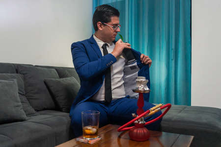 Young man in a blue suit sitting on a sofa. He is putting his mobile phone in a jacket pocket. On the wooden table is a glass with whiskey and a red hookah.