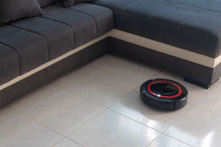 Robot vacuum cleaner automatically cleaning the floor. In the background, there is a couch. Stockfoto