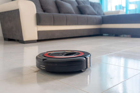 Robot vacuum cleaner automatically cleaning the floor. In the background, there is a couch.
