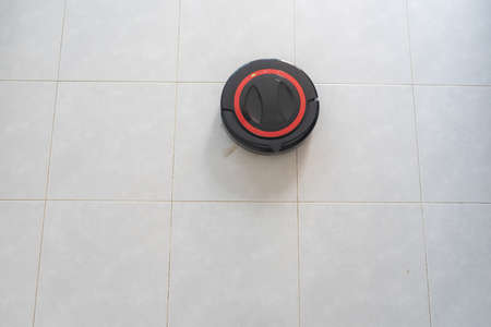 Robot vacuum cleaner cleaning the floor automatically. The intelligent robot is on a white floor.