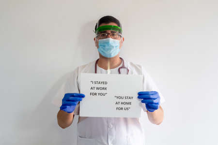 A male nurse with a face protector, mask, gloves and stethoscope. He has a sign that says