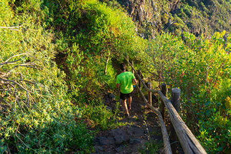 Man practicing trail running. The man runs on a path in a forest. Tenerife is an ideal place to practice outdoor sports.