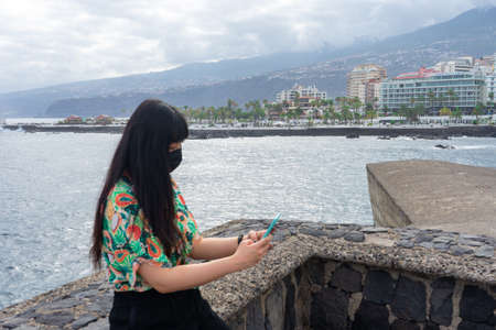 Asian tourist chatting with her smartphone. She does tourism in Puerto De La Cruz, Tenerife. She wears a floral shirt and mask.