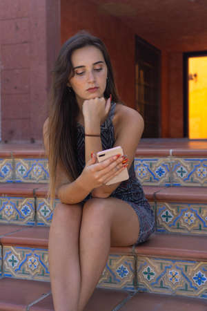 Young woman chatting with an app on her smartphone. She is sitting on some stairs. She wears a short dress. It is located in Las Americas, Tenerife