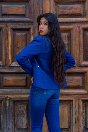 Young woman posing with her hands on her waist. In the background you can see an old wooden door. The photo was taken in La Laguna, Tenerife. Stock fotó