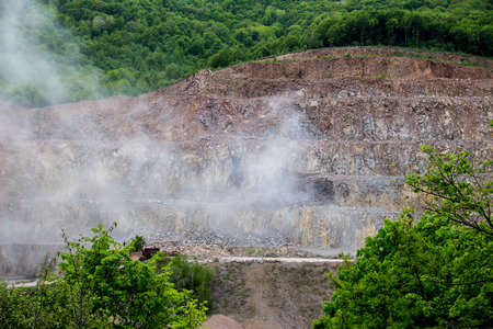layers levels: A small rock mine in Romania, right after an explosion. Smoke dust is rising in the air. Stock Photo